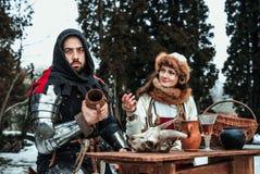 En man och en kvinna i historiska dräkter sitter på en tabell fotografering för bildbyråer
