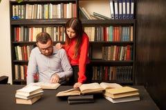 En man och en kvinna läste bildande böcker i arkivet royaltyfri fotografi