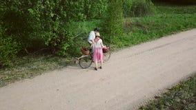 En man och en kvinna med en cykel och korgar promenerar vägen arkivfilmer
