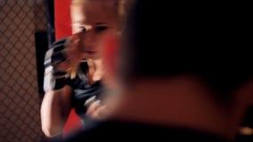 En man och en kvinna munhuggas inom en stridighetbur arkivfilmer