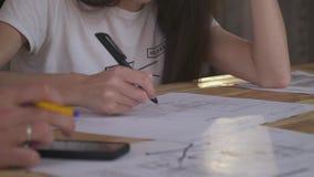En man och en kvinna sitter på en tabell med teckningar som framställning redigerar, tröttade personalen Slut upp skytte stock video
