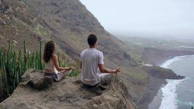 En man och en kvinna som överst sitter av ett berg som ser havsammanträdet på en sten som mediterar i en Lotus position arkivfilmer