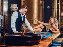 En man och en kvinna spelar i en kasino arkivbilder