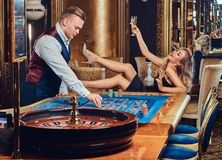 En man och en kvinna spelar i en kasino royaltyfri bild