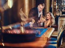 En man och en kvinna spelar i en kasino arkivfoton