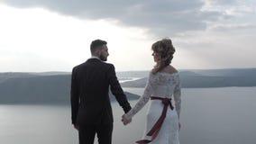 En man och en kvinna står på kanten av klippan nära havet, håret framkallar i vinden vitt arkivfilmer