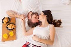 En man och en kvinna vaknade upp i morgonen, frukost i säng fotografering för bildbyråer