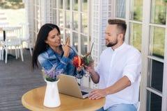 En man och en kvinna vilar i ett kafé, har ett europeiskt utseende, stylishly att kläs, ljusa coctailar för beställningar Flickat royaltyfri foto