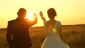 En man och en kvinna visar en hj?rta med deras h?nder p? solnedg?ngen av den guld- solen V?nner p? en romantisk tur teamwork av arkivfilmer