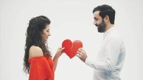 En man och en kvinnahåll två halvor av en bruten hjärta på en vit bakgrund Begreppet av att limma hjärtan kris