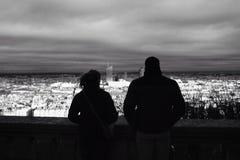 En man och en kvinnlig som tycker om sikten av staden på aftonen arkivfoton