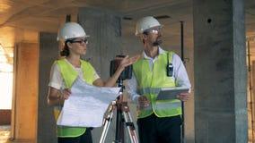 En man och teknikerer för en kvinnlig i mitt av en diskussion i byggnadshuset arkivfilmer