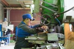 En man på arbete på en vertikal malningmaskin Bearbeta med maskin av en metalldel på enklipp maskin Royaltyfria Bilder