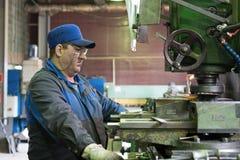 En man på arbete på en vertikal malningmaskin Bearbeta med maskin av en metalldel på enklipp maskin Royaltyfri Foto