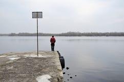 En man på den gamla pir som stirrar på havet royaltyfria foton