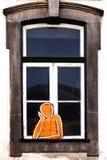 En man på fönstret Arkivfoto