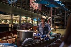 En man på fartyg som svävar marknaden Damnoen Saduak royaltyfria bilder