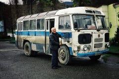 en man på hans buss som används som en campareskåpbil med hans familj som öppnar dörren royaltyfri fotografi