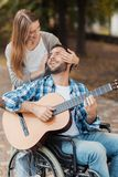 En man på en rullstol som spelar gitarren i parkera En kvinna kom till honom bakifrån och stängt henne ögon med hennes händer Royaltyfri Bild