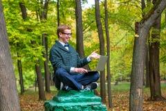 En man på en sockel, som låtsar för att vara en staty i hösten, parkerar royaltyfria foton