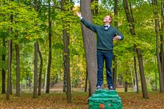 En man på en sockel, som låtsar för att vara en staty i hösten, parkerar royaltyfri fotografi