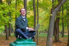 En man på en sockel, som låtsar för att vara en staty i hösten, parkerar royaltyfri bild