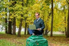 En man på en sockel, som låtsar för att vara en staty i hösten, parkerar fotografering för bildbyråer