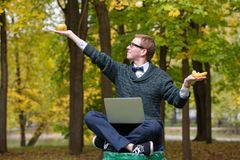 En man på en sockel, som låtsar för att vara en staty i, poserar av en filosof, innan han väljer ett äpple eller en banan i royaltyfri bild