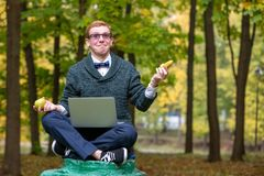 En man på en sockel, som låtsar för att vara en staty i, poserar av en filosof, innan han väljer ett äpple eller en banan i royaltyfria bilder
