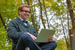 En man på en sockel som låtsar för att vara en staty med en bärbar dator i hand med uttryckt, som den ljusa idén grydde royaltyfri foto
