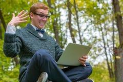 En man på en sockel som låtsar för att vara en staty med en bärbar dator i hand med uttryckt, som den ljusa idén grydde arkivbild
