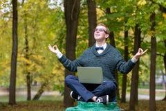 En man på en sockel, som låtsar för att vara en staty, mediterar i lotusblommapositionen i parkerar royaltyfri bild
