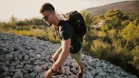 En man på solnedgången stiger till ett berg med en ryggsäck arkivfilmer