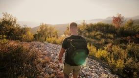 En man på solnedgången stiger till ett berg med en ryggsäck lager videofilmer