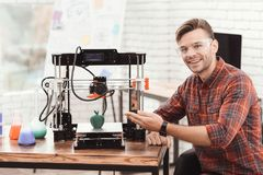 En man poserar nära skrivaren 3d som han skrivev på precis ut en äpplemodell Han är mycket nöjd med resultatet Royaltyfria Bilder