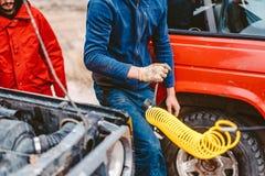 En man pumpar lufthjulet med en kompressor royaltyfri bild