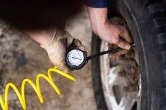 En man pumpar lufthjulet med en kompressor fotografering för bildbyråer