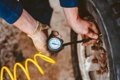 En man pumpar lufthjulet med en kompressor royaltyfri foto
