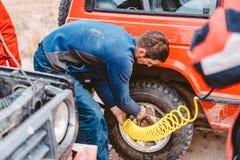 En man pumpar lufthjulet med en kompressor royaltyfria bilder