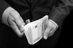 En man räknar pengarna i en packe av sedlar av 500 euro Arkivbilder