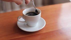 En man rör socker in i en kopp kaffe arkivfilmer