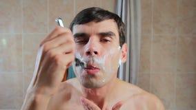 En man rakar hans framsida i skumet med en rakkniv Grabben rakar framme av en spegel lager videofilmer