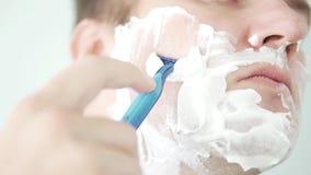 En man rakar hans kind med en blå rakkniv lager videofilmer