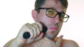 En man rakar hans kind med en rakapparat, på en vit bakgrund lager videofilmer