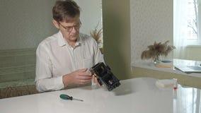 En man reparerar endanande enhet av en kaffemaskin, reparation shoppar av kaffebryggare lager videofilmer