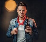 En man rymmer en flaska med hantverköl royaltyfri foto