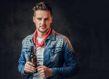 En man rymmer en flaska med hantverköl royaltyfria foton