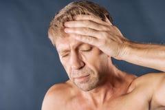 En man rymmer hans händer på hans huvud på blå bakgrund Huvudvärk eller migrän royaltyfri fotografi