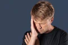 En man rymmer hans händer på hans huvud på blå bakgrund Huvudvärk eller migrän arkivbilder