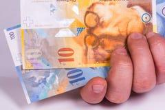 En man rymmer i hans hand en schweizisk sedelnärbild arkivbild